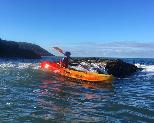 Sea kayaking playing with waves rock hopping